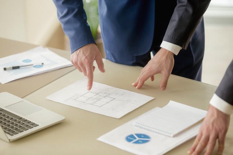 Adviseur legt een plan uit voor een huis kopen op de zaak